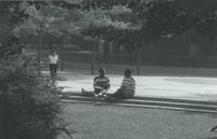 Two students sitting on some steps near the Centennial Student Union at Mankato State University