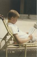A student sitting in a chair reading a book outside of the Centennial Student Union at Mankato State University