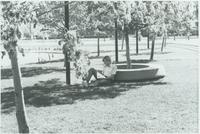 A student sitting next to a tree reading at Mankato State University