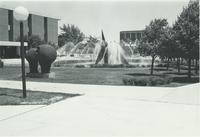 A picture of the Mankato State University Memorial Library, Chthonic Sculpture, Armstrong Hall and students walking on the campus mall, 1980s.
