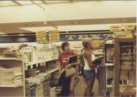 A picture of two Mankato State University students looking at textbooks in the MSU bookstore, 1985.