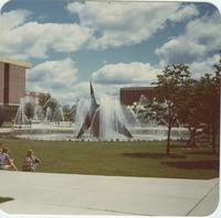 A picture of Mankato State College students relaxing and walking through the fountain and campus mall area, 1980s.