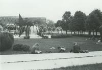 Mankato State University students sitting the grass near the fountain studying, 1980s.
