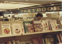 A picture of a Mankato State University student looking at textbooks in the MSU bookstore, 1985.