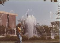 A Mankato State University student walking by the university fountain, 1980s.