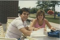 Two students sitting at a table near the Centennial Student Union and the Waves Sculpture in the background at Mankato State University