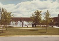 Mankato State University students sitting by the fountain and walking in the campus mall, 1970s.