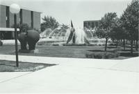 A picture of the Mankato State University fountain, Memorial Library, campus mall, Armstrong Hall academic building and Chthonic Sculpture, 1980s.