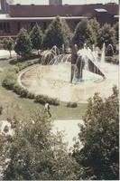 A picture of a Mankato State University student walking by the campus fountain and Centennial Student Union, 1980s.