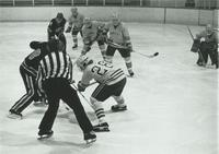 A picture of a referee dropping a puck during a Mankato State College Maverick men's hockey game, 1970s.