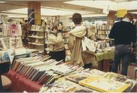 A picture of three people looking at textbooks in the Mankato State University bookstore, 1985.