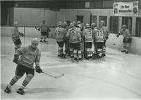 A picture of the members of the Mankato State College Maverick men's hockey gathered around each other talking, 1970s.