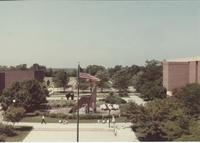 A picture taken from the Armstrong Hall academic building of Mankato State College students walking on the Campus Mall, 1980s.