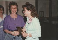 Carolyn Jewison shaking hands with some people from admissions after receiving the student employee of the year award at Mankato State University