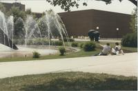 A picture of Mankato State University students relaxing around the university fountain and Centennial Student Union building, 1980s.