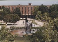 A picture of Mankato State University students walking on the Campus Mall between the university fountain and Armstrong Hall academic building, 1980s.