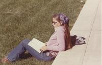 A student, enjoying the weather outside, reading a book at Mankato State College
