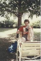 A student sitting under a tree reading a book at Mankato State University