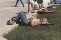 Students sitting/laying on a curb reading at Mankato State University