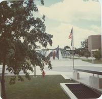 A picture taken from Armstrong Hall of Mankato State University students walking on the Campus Mall near the university fountain and Memorial Library, 1980s.