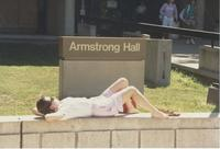A student laying down in front of the Armstrong Hall sign at Mankato State University