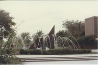 A picture of the Mankato State University fountain, Memorial Library and Waves sculpture taken from the Campus Mall, 1980s.
