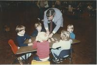 A man talking with some children during the Minnesota Valley Association for the Education of Young Children conference held in the Mankato State University Centennial Student Union, 1991.