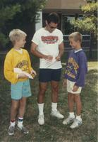 Two kids getting an autograph from Minnesota Vikings team member Chuck Nelson at Mankato State University