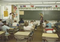 One teacher at the blackboard and one teacher assisting a student with a classroom of young students, Mankato State University.