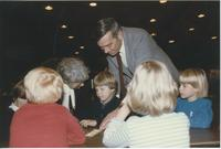 Jean Peterson (left) Children's House assistant director, director, 1974, shown bending over with another man talking with some children during the 1991 Minnesota Valley Association for the Education of Young Children Conference in the Mankato State Unive