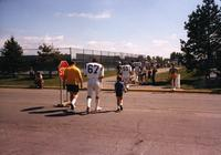 Evan Rusch walks with Minnesota Vikings Player Denis Swilley #67 at Mankato State University, August 1983.