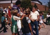 Vikings Fans approach Minnesota Vikings players near Myers Fields House and asks for autographs at Mankato State University, August 1983.