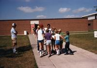 Fans circling MN Vikings Player Leo Lewis at Mankato State University, August 1983.