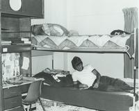Student reading a magazine in his Gage Center dorm room at Mankato State University