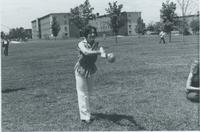 Female throwing a ball on front lawn of Performing Arts Center, Mankato State University.