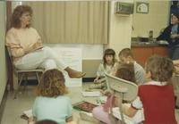 A student teacher working with young students in a classroom, Mankato State University.