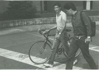 Student walking his bike  with another student, Campus Mall, Mankato State University