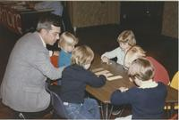 A man sitting at a table with some children during a 1991 Minnesota Valley Association for the Education of Young Children event in the Mankato State University Centennial Student Union.