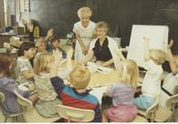 A student teacher in a classroom with a teacher and enthusiastic students, Mankato State University.