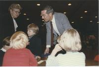 Jean Peterson (left) Children's House assistant director, director, 1974, and another man standing with some children during the 1991 Minnesota Valley Association for the Education of Young Children Conference in the Mankato State University Centennial St