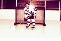 Mankato State University Maverick men's hockey player, number 10, posing for a picture in front of a hockey net, 1980s.