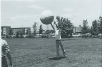 Students playing with a large ball at the New Games Institute and Tournament, Performing Arts Center lawn, Mankato State University.
