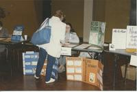 Two women speaking at the Head Start Education booth in the Minnesota Valley Association for the Education of Young Children conference in the Mankato State University Centennial Student Union, 1991.