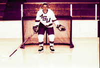 Mankato State University Maverick men's hockey player posing for a picture in front of a hockey net, 1980s.