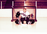 A goalie for the Mankato State University men's Maverick hockey team posing for a picture in front of a hockey net, 1980s.