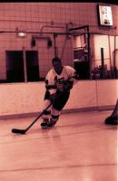 A picture of Mankato State University Maverick men's hockey player, number 34, skating around a hockey net, 1980s.