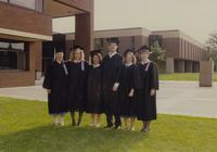 Six unknown graduates, five women and one man at Mankato State University taking picture in front of Earle J. Wigley Administration Building. 06-07-1991.