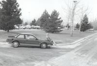 Unidentified man sitting on the front of car Mankato State University April 10, 1991.