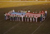 Girl scouts are holding the American Flag at the football game MSU VS GVSU at Mankato State University, 1990-09-15.