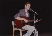 Unknown male is playing guitar and singing at Mankato State University, 1990-07-12.